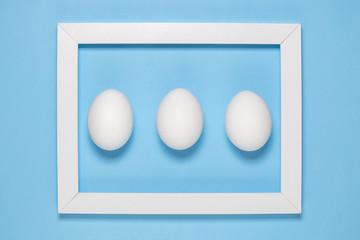 White egg and photo frame on plain blue background