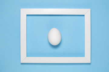 White egg and photo frame on plain blue background