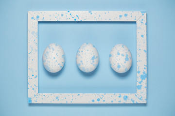 White eggs and artistic frame on plain blue background
