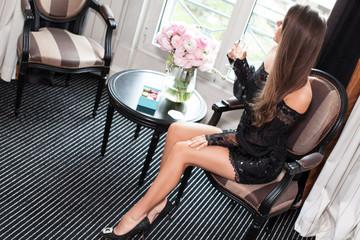 Beautiful young woman in black mini dress