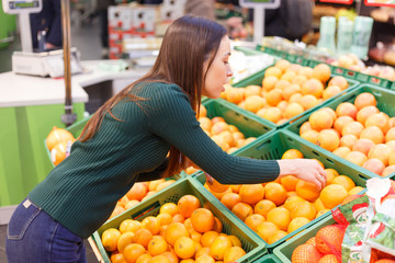 A young woman in a store chooses oranges.