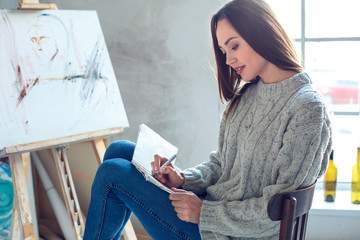 Young woman artist painting at home creative sketch