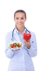 Portrait of a beautiful woman doctor holding a plate with fresh vegetables and red heart. Woman doctors.
