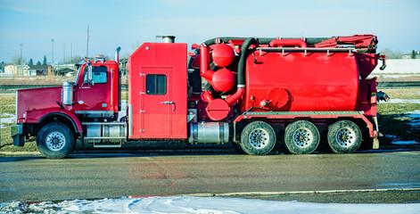 Big, red hydro vacuuming excavation track on thr road