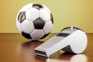 Football ball with whistle on the wooden table, 3D rendering