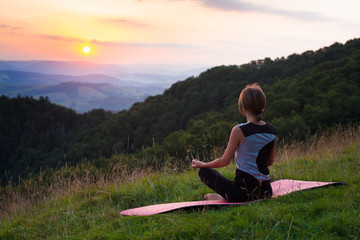 Woman doing yoga meditation in the mountains at dawn