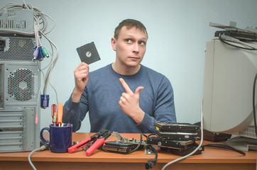Computer technician engineer is holding in one hand a backup diskette disk and is showing on it by his other hand..Do not forget making a database information backup reminder concept.