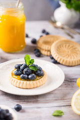 Homemade shortbread tartlet with lemon curd and fresh blueberries on white wooden background. Holiday food concept.