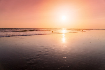 Beach in sunset with people