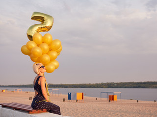 Young woman with many golden balloons.