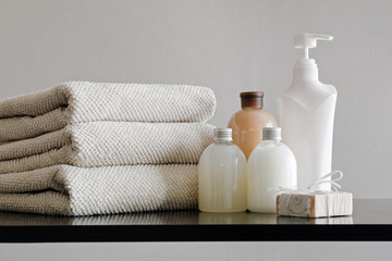 Obraz Pile of towels, bottles with shampoo, body lotion, shower milk and handmade soap on neutral background. - fototapety do salonu