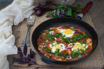 Shakshuka or fried eggs with tomatoes.
