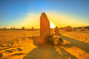 Giant limestone formation illuminated by red sunset light. Pinnacles Desert in Nambung National Park, Western Australia.During late afternoon and sunset the Pinnacles are illuminated by the best light