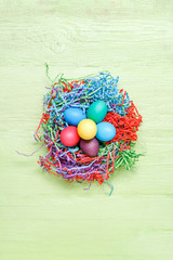 Image of multi-colored Easter eggs on green wooden background