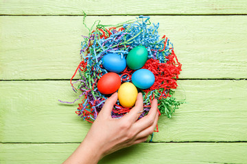 Image of multi-colored Easter eggs and hand on green wooden background