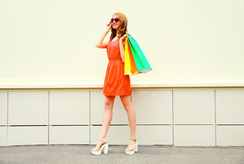 Fashion pretty smiling woman in red dress with a shopping bags in the city