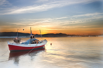 Small boat on a sea at sunset.