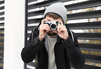 Trendy hipster man taking photo outdoors
