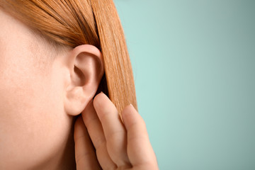 Young woman with hearing problem on color background, closeup Wall mural