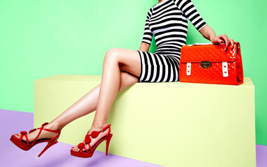 Beautiful legs woman with red heels with orange bag sitting on the yellow bench