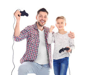Happy man and his son with video game controllers on white background