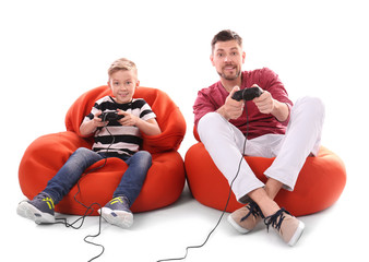 Cute boy with father playing video game on white background