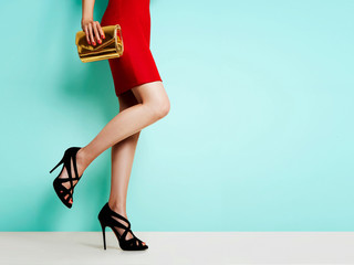 Wall Mural - Woman with beautiful legs with red skirt, black heels shoes, gold wallet. isolated on bright blue background.