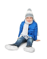 Cute little boy in warm clothing on white background. Ready for winter vacation