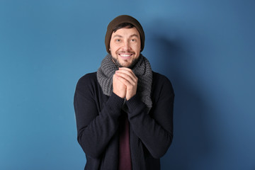 Young man in warm clothing on color background. Ready for winter vacation