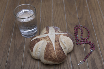 symbols of lent, bread and water on wooden table in dark room
