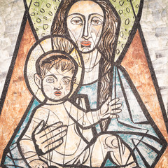 Virgin Mary with baby Jesus painted on a wall of the ancient cemetery of San Candido.