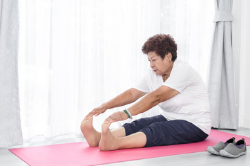 Asian senior woman doing exercise at home.