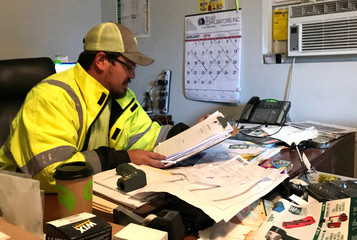 Ortega, a supervisor at an infrastructure safety company, reviews budget paperwork in San Antonio