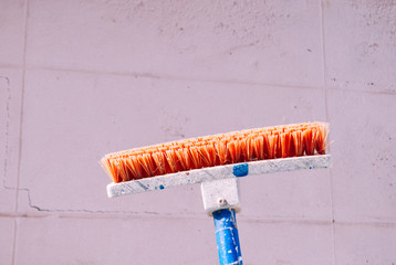 Orange cleaning brush on the concrete wall