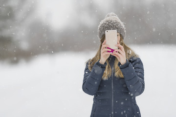 Chica con movil un dia de nieve
