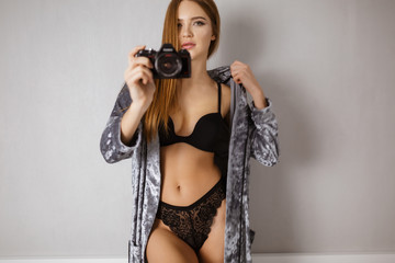 Beautiful pensive woman in black lingerie and velvet robe standing with camera in hand isolated