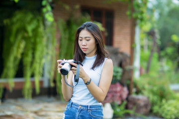 Asian girl checking photo on camera