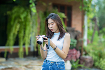 Young asian girl checking photo on camera