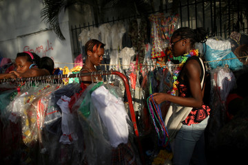 Women look for goods at stands with costumes in Port-au-Prince
