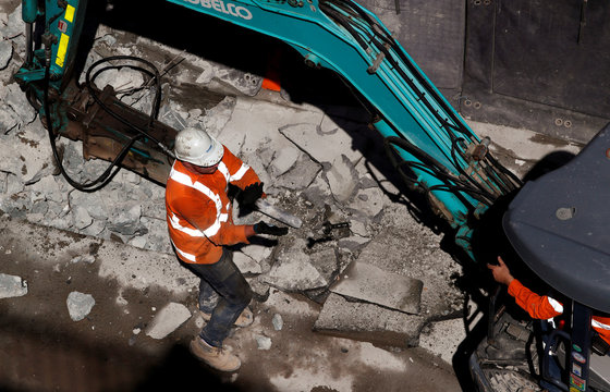 A construction catches a tool at a construction site in central Sydney