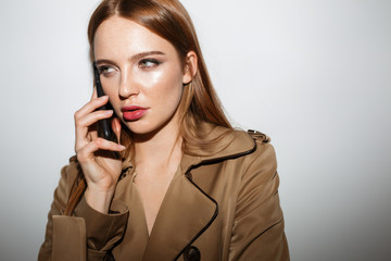 Young pretty woman in trench coat standing and dreamily looking aside while talking on her cellphone isolated