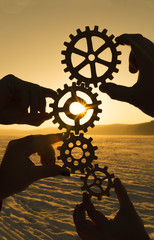 four hands are holding the gears against the sunset. teamwork. harmonious work.