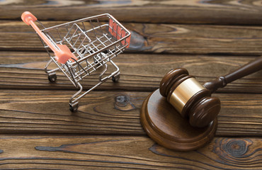 hammer of the judge, a trolley from a supermarket on a wooden background. consumer rights Protection.