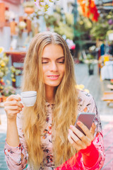 Beautiful woman is enjoying a cup of coffee and checking a mobile phone in the cafe