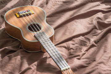 Ukulele guitar on bed background., copy space for text., girl enjoy with her ukulele. music concept. teaching concept. relax concept. hobby concept..