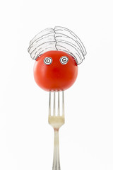 Single red tomato on white background with turban sitting as a fakir on top of a silver fork representing indian food.