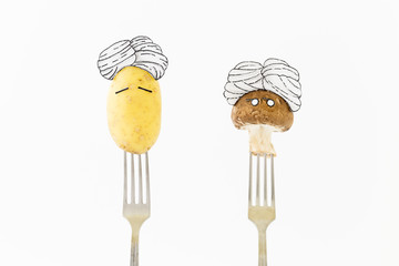 Potato and mushroom on white background with turban sitting as fakir on top of silver forks representing indian food.