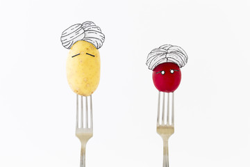 Potato and red radish on white background with turban sitting as fakir on top of silver forks representing indian food.