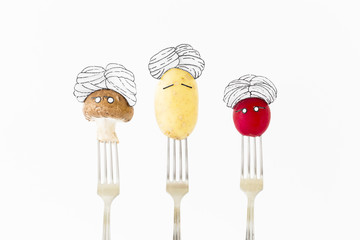 Potato, red radish and mushroom on white background with turban sitting as fakir on top of silver forks representing indian food.