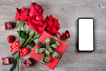 Happy Valentine's Day Concept with red roses, gift boxes, smartphone and space for text